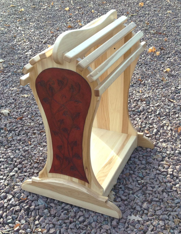 Red Saddle Stand made out of hickory with leather tooling on the front.